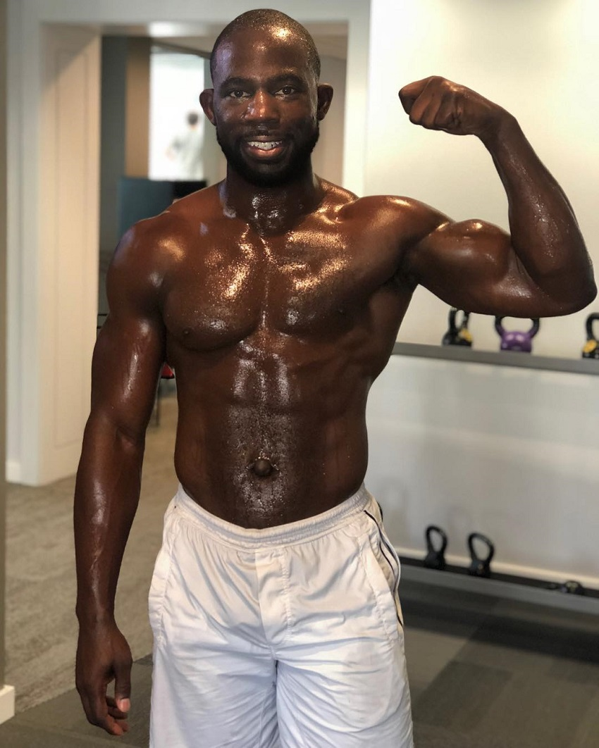 Gideon Akande flexing his biceps and showing off his sweaty and ripped body after a workout
