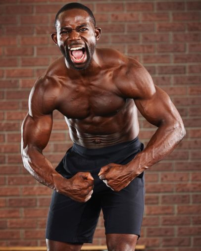 Gideon Akande flexing his muscles for a photo with a yelling grimace