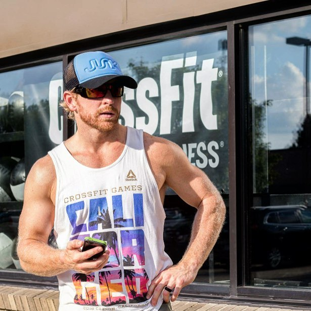 Graham Holmberg standing in front of a CrossFit gym in his summer tank top