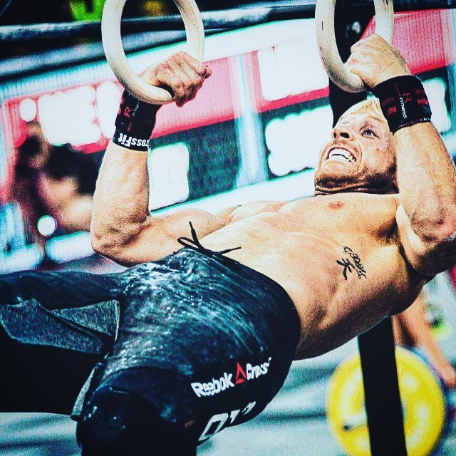 Graham Holmberg hanging on rings with his hands during a CrossFit competition