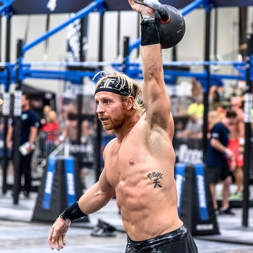 Graham Holmberg lifting a kettlebell over his head during a CrossFit competition