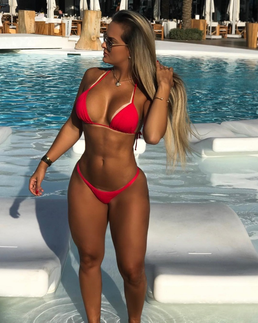 Maira Reis posing by the pool in a red bikini looking fit and lean
