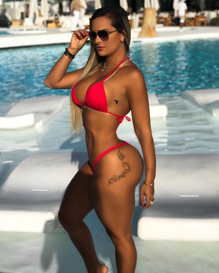 Maira Reis standing by the pool in her red bikini, looking fit and lean