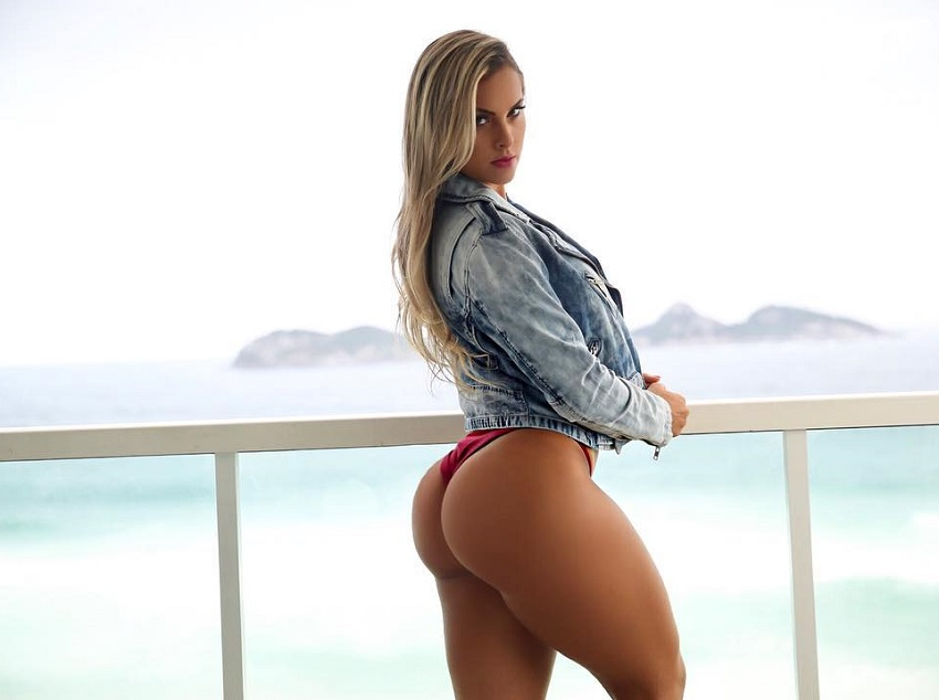 Maira Reis posing on a balcony showcasing her awesome glutes