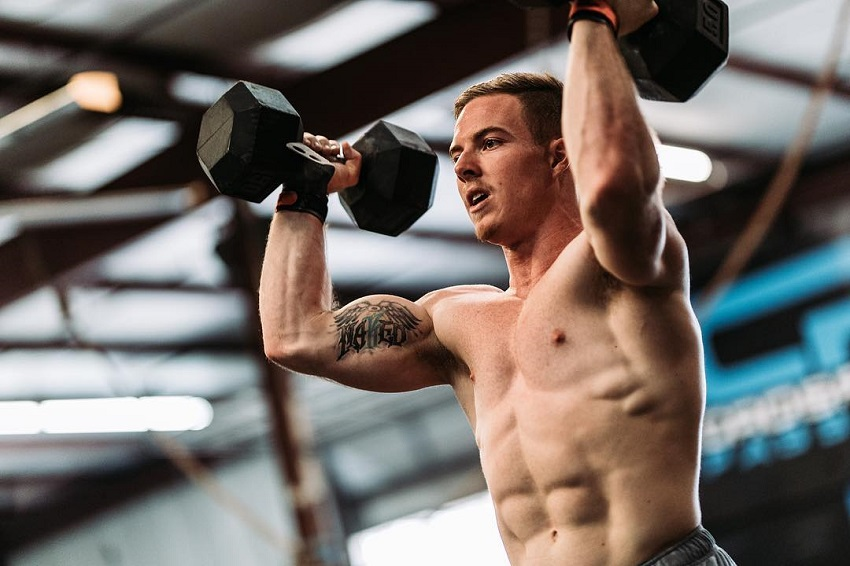 Noah Ohlsen training hard with dumbbells his shirtless body looking ripped and strong