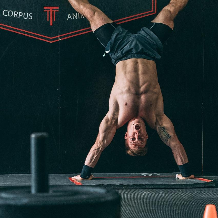 Noah Ohlsen doing a shirtless handstand