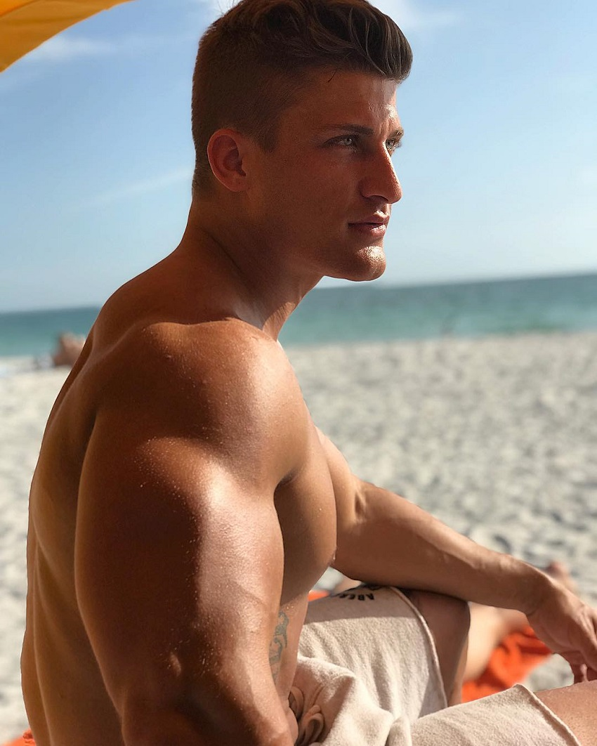 Quinn Biddle sitting on a beach posing for a photo, looking strong and lean