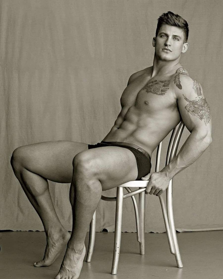 Quinn Biddle sitting shirtless on a chair posing in a modeling photo shoot