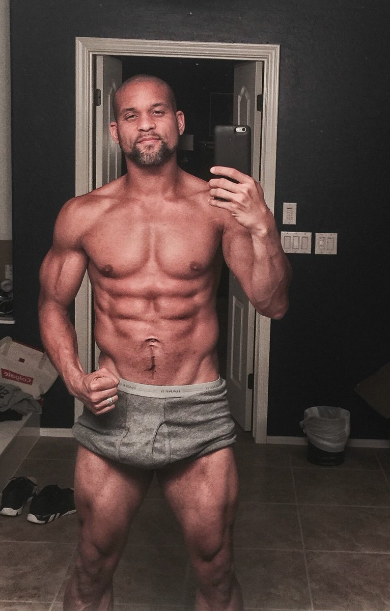 Shaun T taking a selfie of his strong and ripped physique