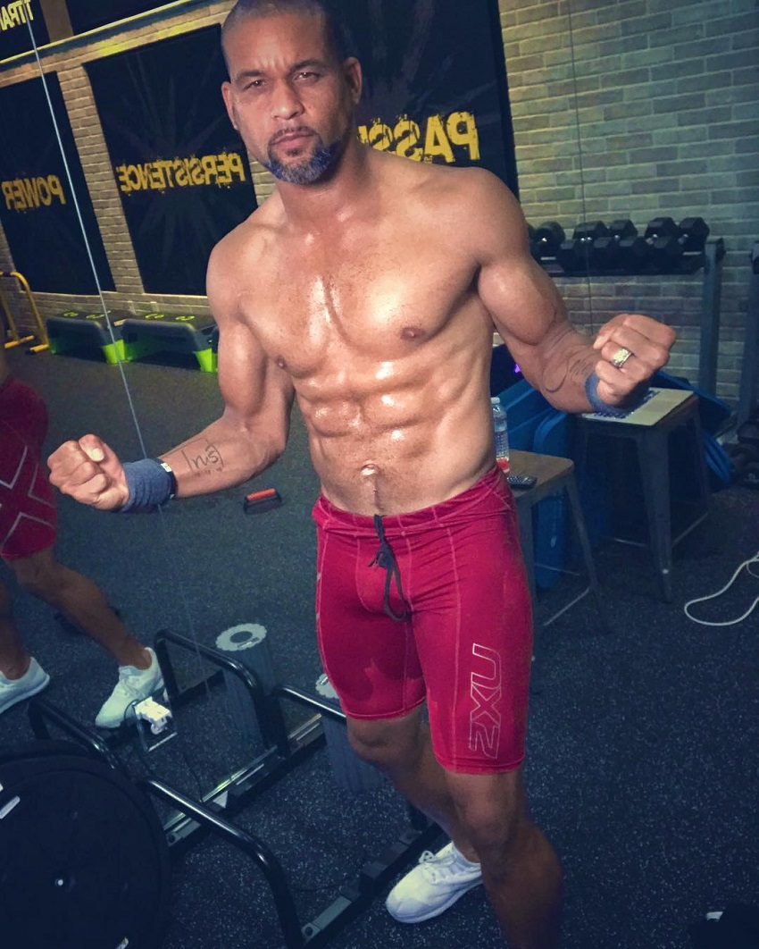 Shaun T flexing his shirtless upper body for a photo