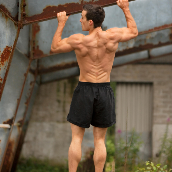 Scott Baptie doing pull ups while shirtless looking ripped and muscular