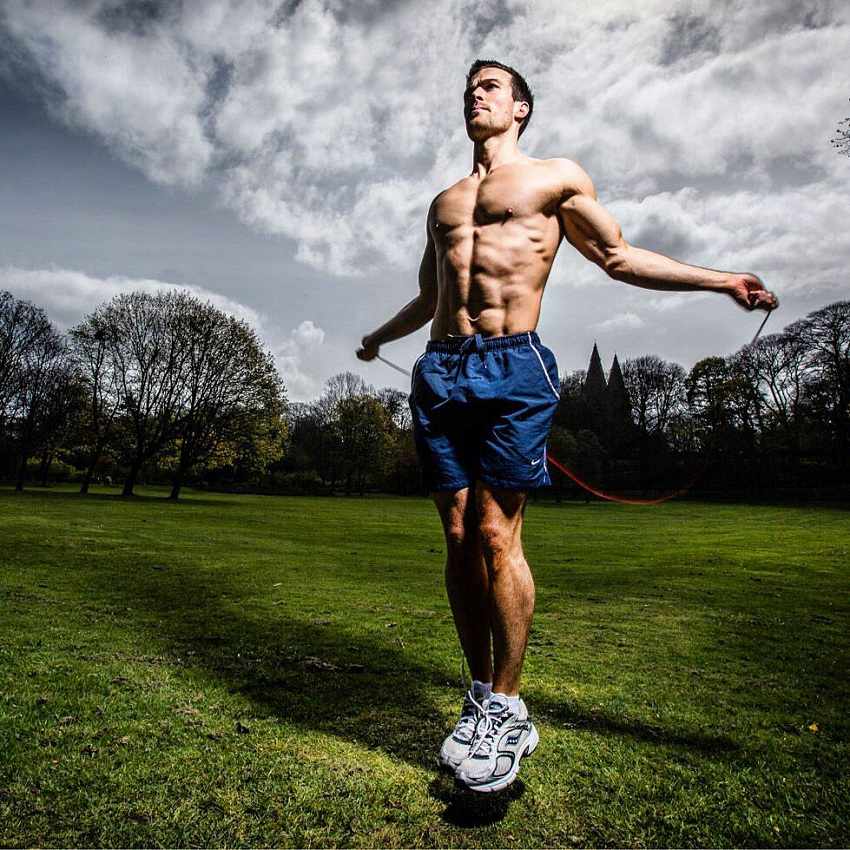 Scott Baptie performing jumping ropes shirtless in the grass field