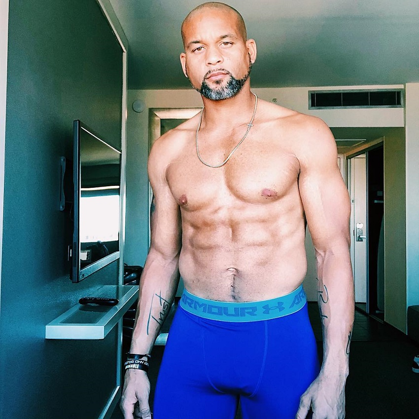 Shaun T displaying his shirtless upper body for the camera looking strong and lean