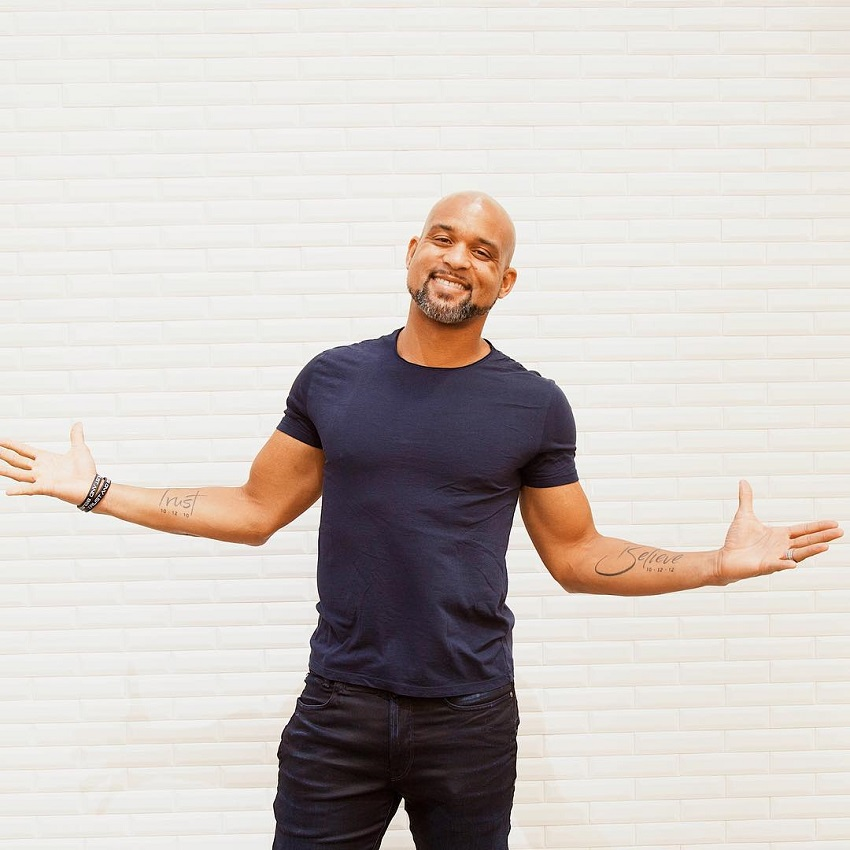 Shaun T posing in his dark blue t-shirt, looking healthy and strong