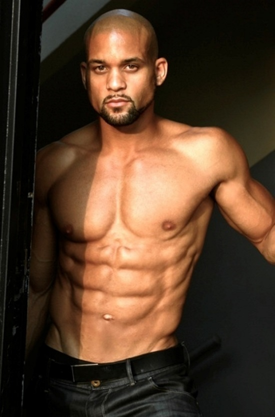 Shaun T posing shirtless for a photo looking strong and lean