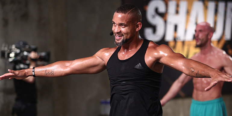 Shaun T during a fitness boot camp wearing a black tank top, looking fit anad muscular