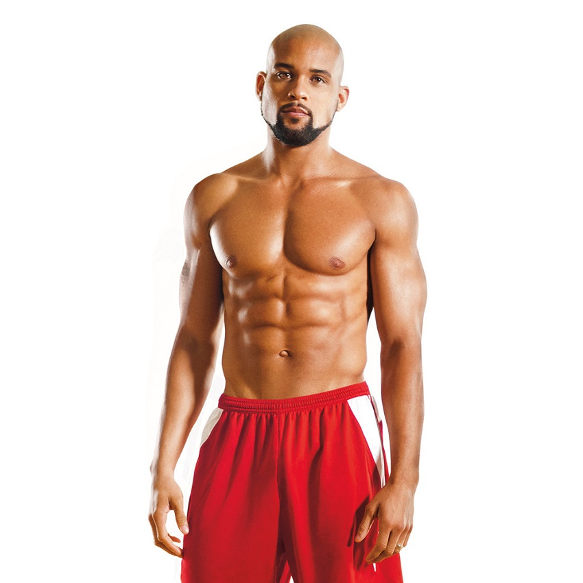 Shaun T showing off his muscles in a fitness photo shoot