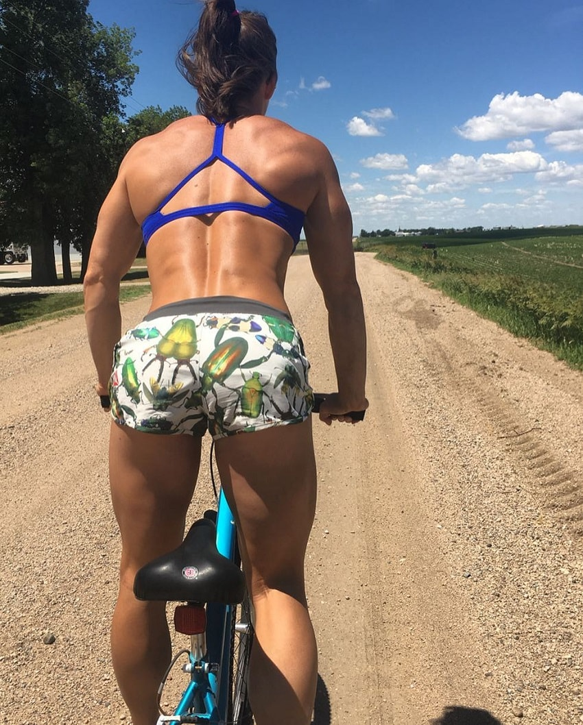 Stacie Tovar riding a bicycle her back looking muscular and fit