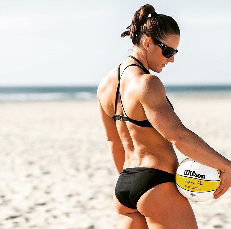 Stacie Tovar standing on a beach in a black swim suit with a volleyball in her hand, looking muscular and curvy