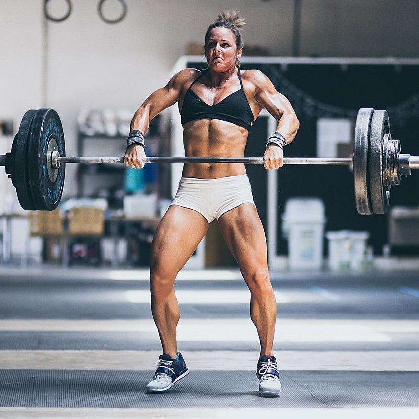 Stacie Tovar lifting heavy barbell with weights during CrossFit training