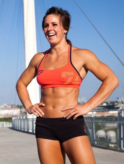 Stacie Tovar smiling while standing on top of a building, looking fit and ripped