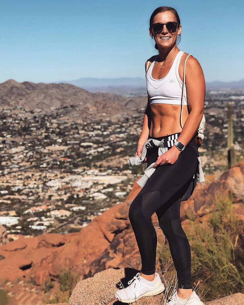 Tanya Poppett standing on the cliff overlooking a town looking fit and lean