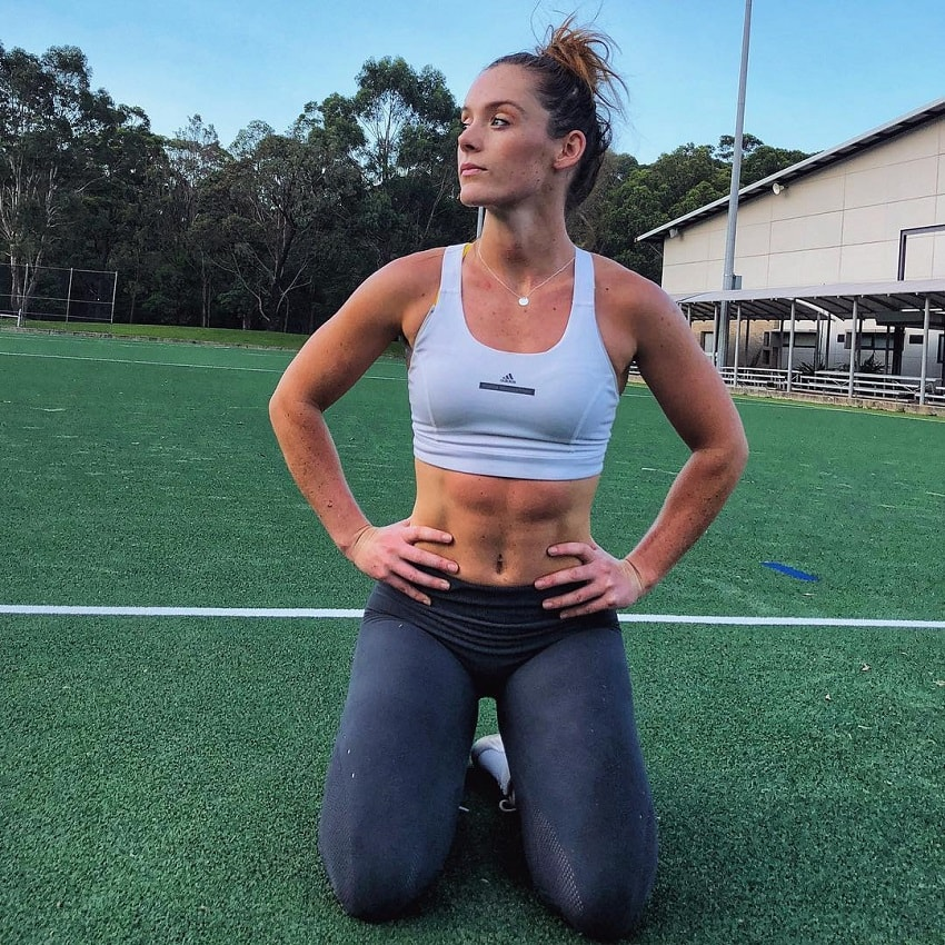 Tanya Poppett kneeling on a soccer field looking fit and lean