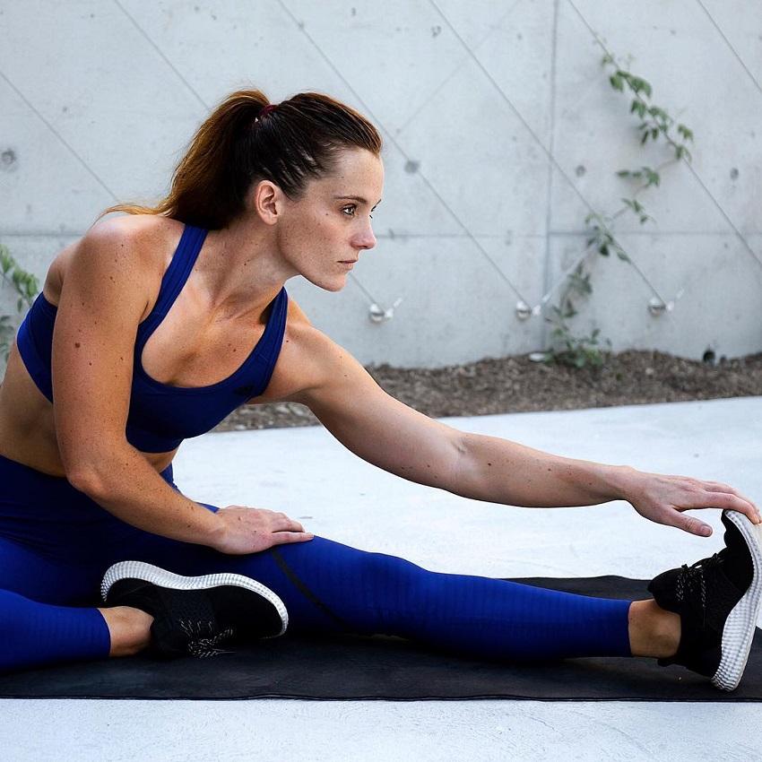 Tanya Poppett stretching her legs on a black yoga mat