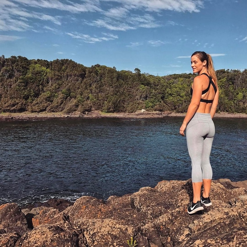 Tanya Poppett standing on the rock overlooking a river, wearing grey leggings