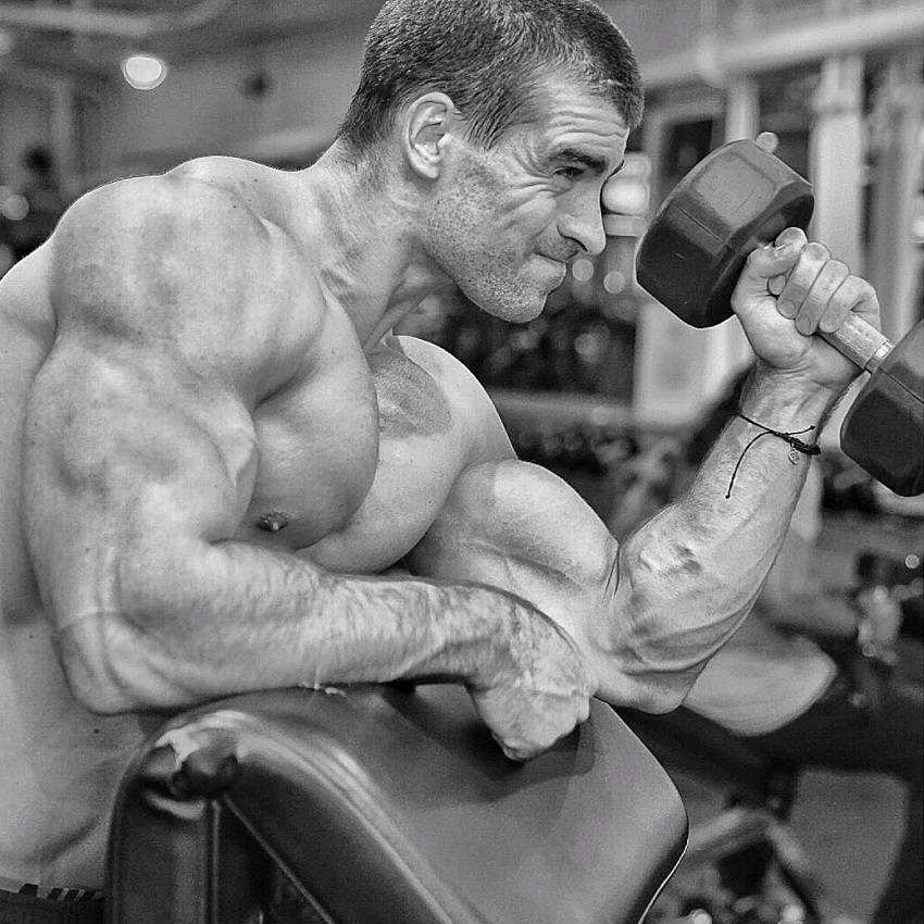 Thomas Canestraro doing heavy dumbbell biceps curls while being shirtless, looking strong and ripped