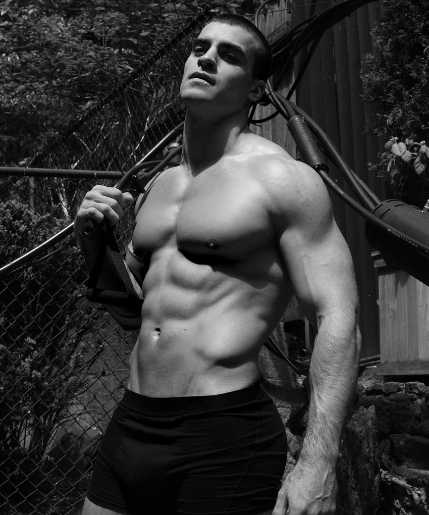 Thomas Canestraro posing shirtless, displaying his lean and muscular body in a professional photo shoot