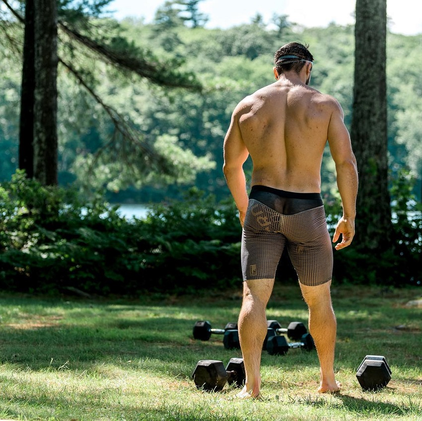 Travis Williams standing in the nature with trees and dumbbells on the grass, his back looking muscular and lean