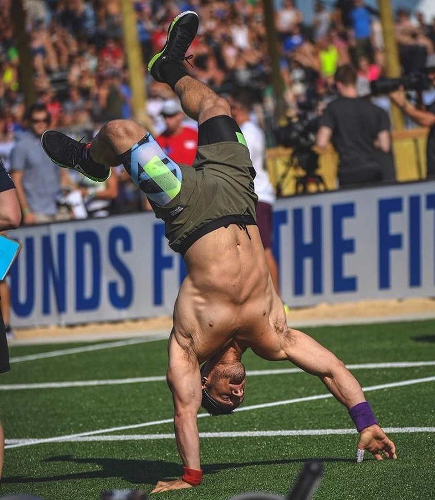 Travis Williams doing a handstand during a CrossFit competition, looking strong and lean