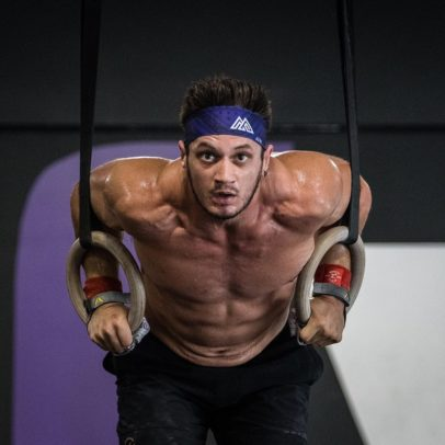 Travis Williams performing CrossFit ring dips, looking ripped and fit
