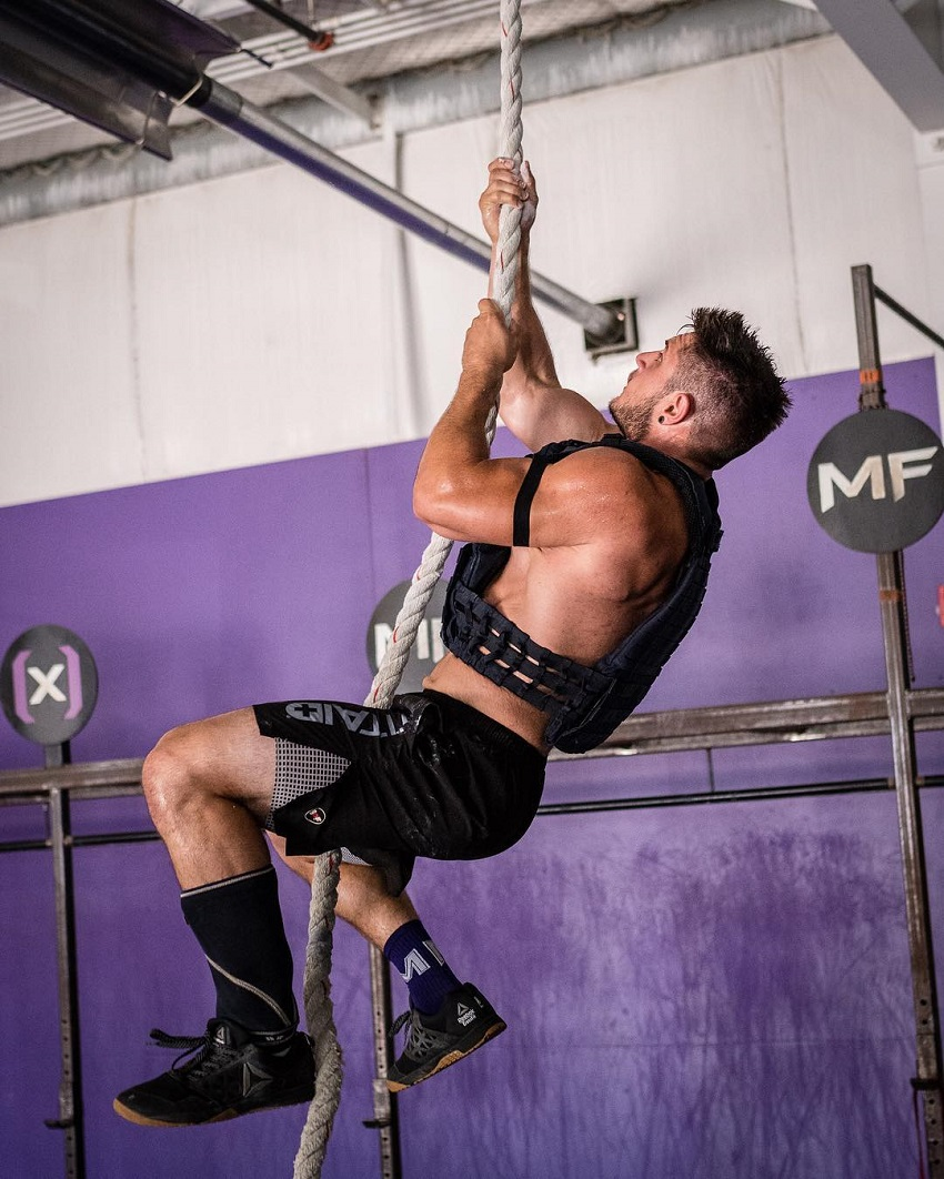 Travis Williams climbing a rope during CrossFit training