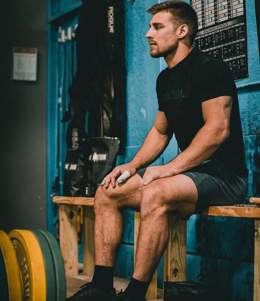 Alex Anderson sitting on a wooden chair looking strong and fit