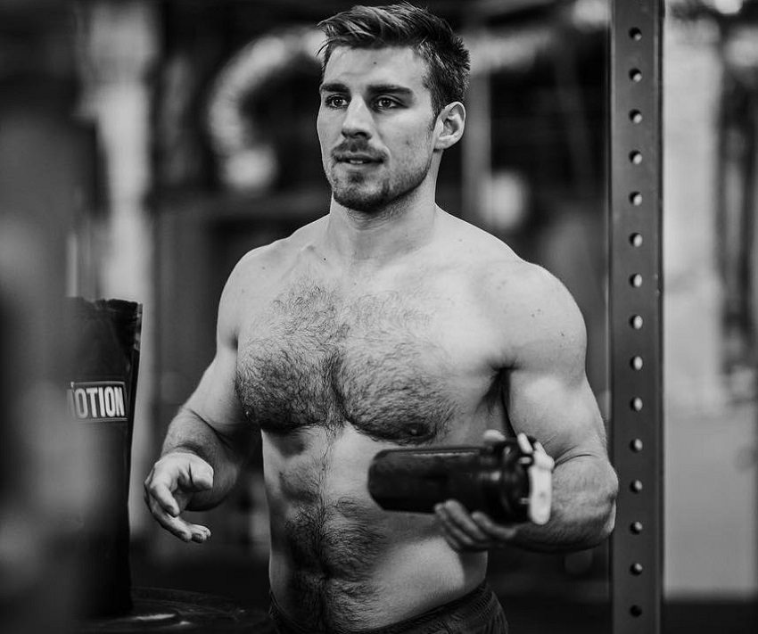 Alex Anderson shaking his shaker bottle after training, his shirtless body looking strong and ripped