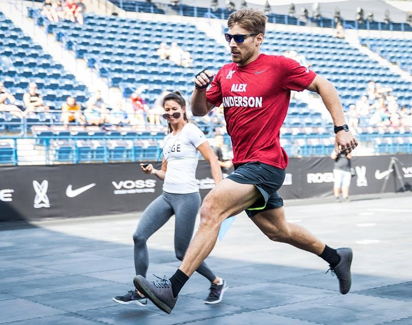 Alex Anderson running on a track with a female by him