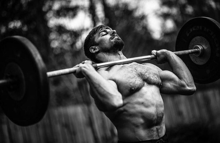 Alex Anderson lifting a heavy barbell while being shirtless, looking strong and ripped