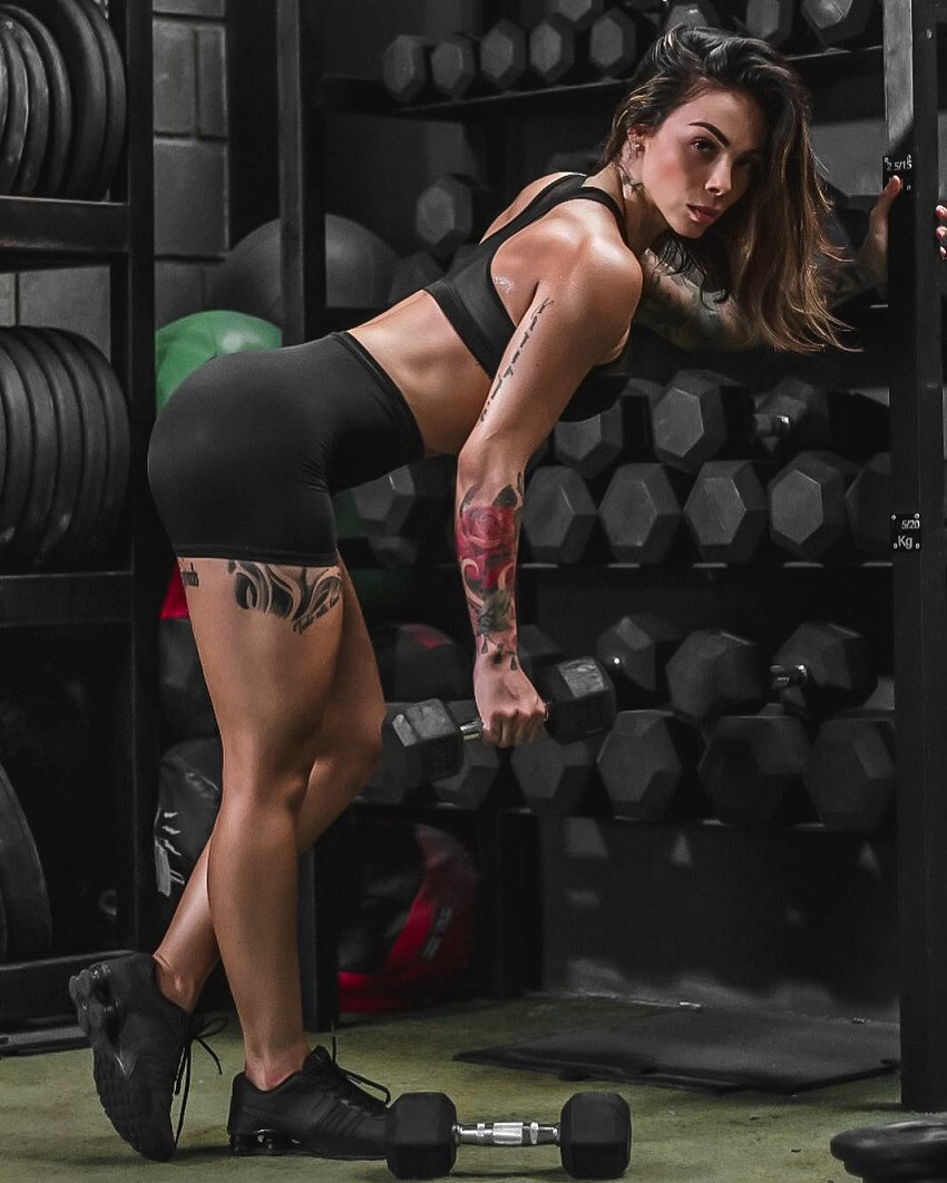 Angelica Fernandez posing by a dumbbell rack with a dumbbell in her hand