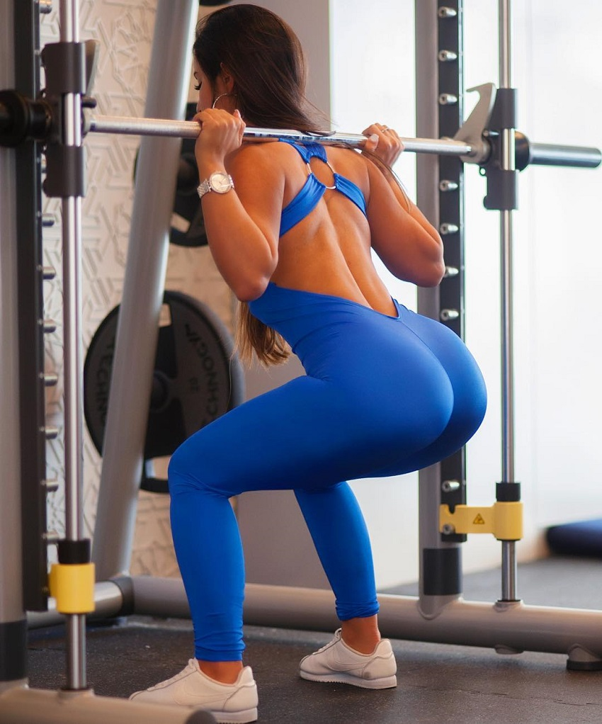 Avital Cohen doing smith machine squats in her blue leggings looking curvy and fit