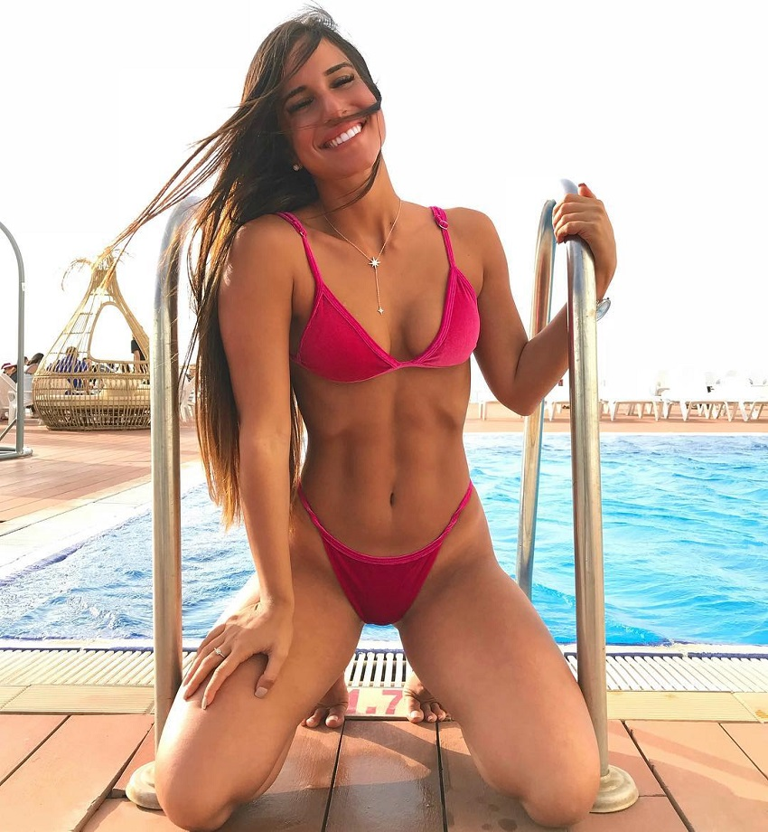 Avital Cohen kneeling by a pool looking fit and lean