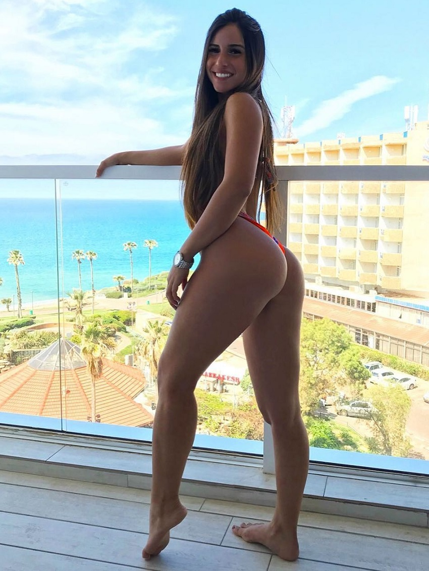 Avital Cohen posing on a balcony in her bikini during a vacation, looking fit and curvy