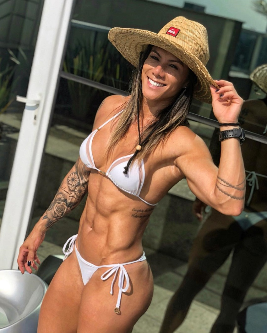 Carolinne Hobo posing and smiling for a photo in her white bikini, showing off her ripped and bulging abs