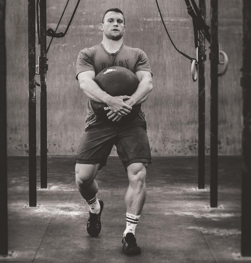 Chad Mackay carrying a heavy ball during CrossFit training looking strong and fit