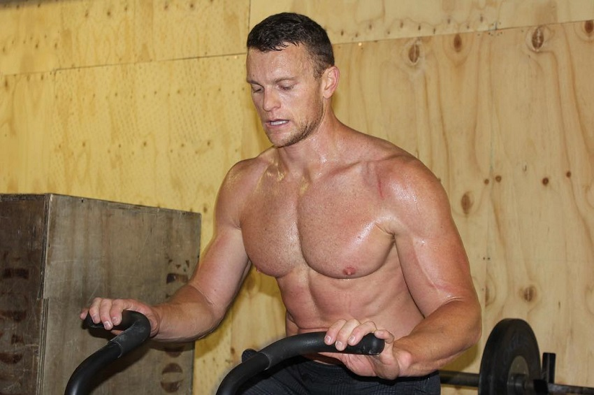 Chad Mackay exercising shirtless on a stationary bike looking lean and strong