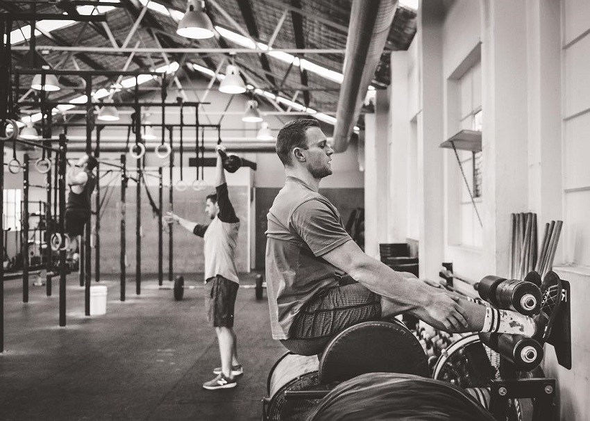 Chad Mackay sitting in a CrossFit gym preparing to do heavy weightlifting