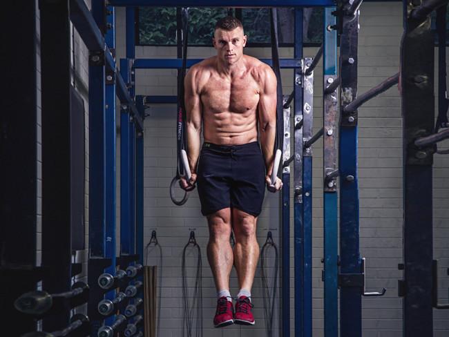 Chad Mackay performing ring exercises shirtless