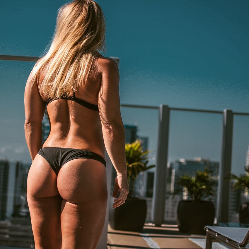 Dani Elle Speegle posing for a photo in her swimsuit showing off her muscular back and curvy glutes