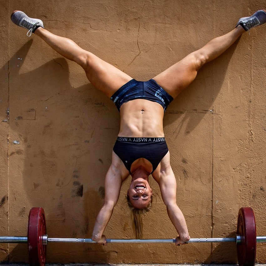 Dani Elle Speegle doing a wall-supported handstand on a barbell loaded with weights
